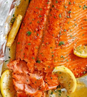 Salmon fillet in foil, with honey garlic sauce and topped with lemon wedges.